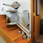 Powered folding hinge rail for stairlifts